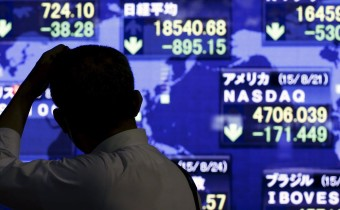 A-man-looks-at-market-indices-at-a-stock-quotation-board-outside-a-brokerage-in-Tokyo